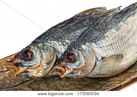 Dried salted bream fish on the brown plate. Close up.