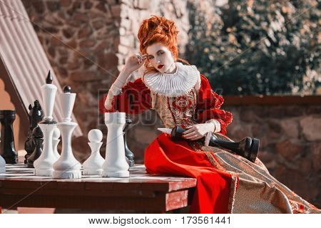 The gothic Red Queen is playing chess. Red-haired woman in a chic vintage gothic dress. Fashion Photo