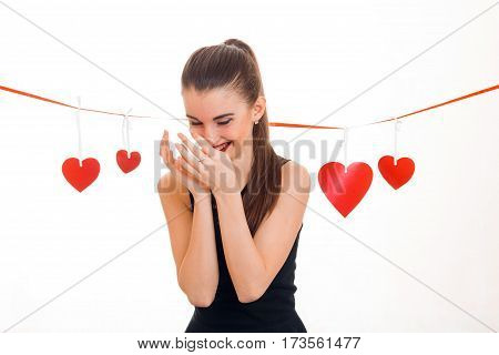 a cheerful young girl stands near Red Ribbon with hearts hanging its head down and keeps hands near individuals is isolated on a white background