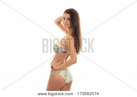 young girl with nice sexy body in swimsuit worth turning sideways to the camera isolated on white background
