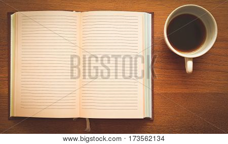 open notebook and cup of coffee on the unfinished wooden table