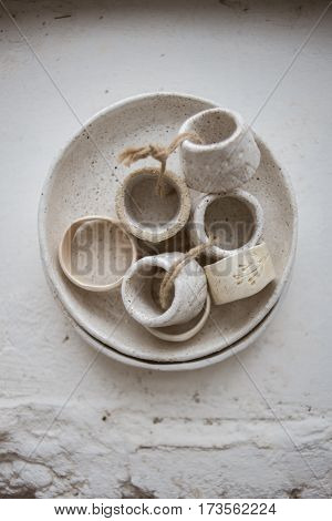 Top view on grog clay plate with beautiful rustic napkin rings on white background