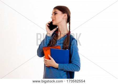 young girl in blue jacket on the phone and keeps the packs in hand isolated on white background