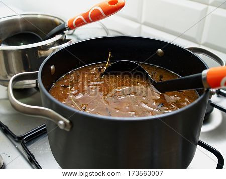 Cooking traditional French onion gratin soup in a pot on a gas stove