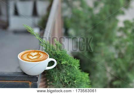 Coffee Cup With Latte Art On The Metal Fence