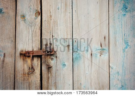 Old wooden door with rusty lock and old latch
