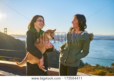 same sex lesbian couple with pet dog shiba inu on hills in front of golden gate bridge