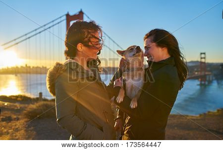 lesbian couple with shiba inu pet dog in front of golden gate bridge at sunrise