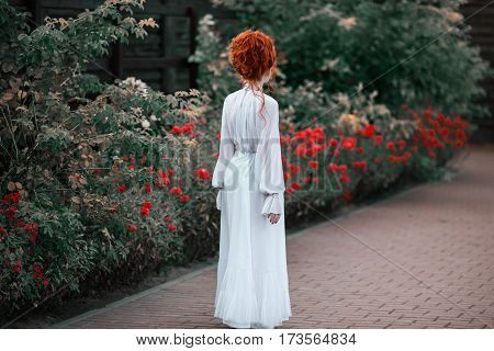 Beautiful red-haired girl with a high hair in an old white dress in the park back. The Victorian era. Historic costume. White Queen. Princess castle. Woman back