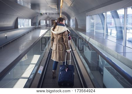 Young woman in airport carrying a suitcase on the conveyor to airplane gate