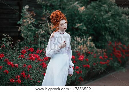 Fairytale of beautiful red-haired girl with a high hair in an old white dress in the park. The Victorian era. Historic costume. White Queen. Princess castle fairytale