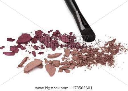 Close up of crushed eyeshadow burgundy color palette with makeup brush on white background. Trendy eye makeup