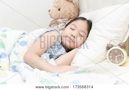 Adorable little girl sleeping in the bed with alarm clock