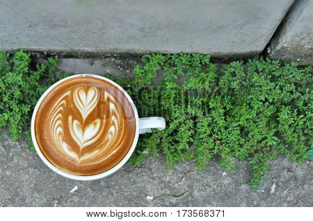 Coffee Cup With Latte Art On The Concrete Floor