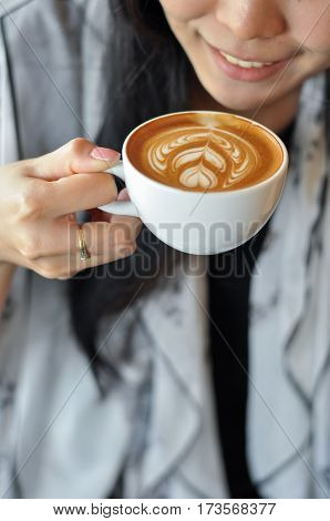 Smiling female holding coffee with latte art.
