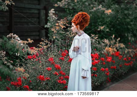 Beauty photo in park. Beautiful red-haired girl with a high hair in an old white dress in the park. The Victorian era. Historic costume. White Queen. Princess castle. Historic beauty style. Photography in beauty style. Beauty concept. Princess fashion dre