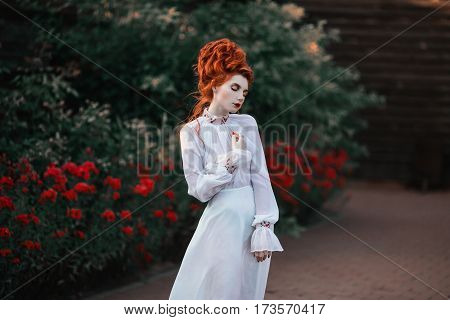 Beautiful aristocrat redhead girl with a high hair in an old white dress in the park. The Victorian era. Historic costume. White Queen. Princess aristocrat castle. Redhead aristocrat model