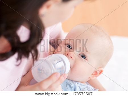 Mother feeding her baby son with bottle