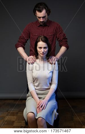 Young couple, woman is sitting on the chair, the man is standing behind, his hands keeping her shoulders, gray background