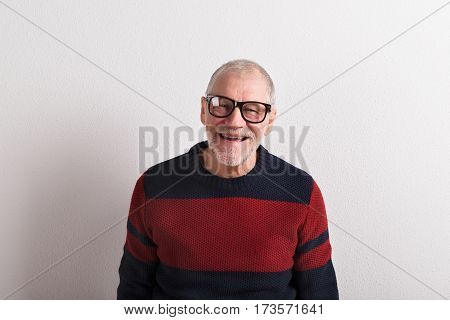 Handsome senior man in red and blue sweater and black eyeglasses, smiling. Studio shot against white wall.