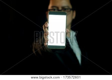 Asian Man in the Dark Shows smart phone with copy space.