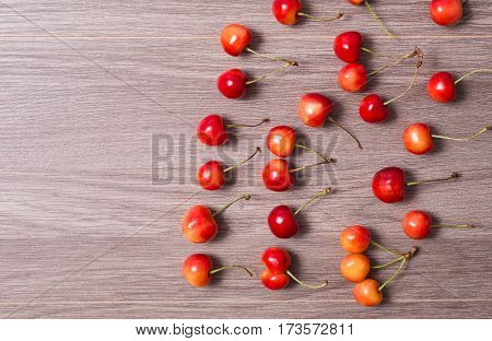 Ripe red and yellow cherries lie on a wooden background.