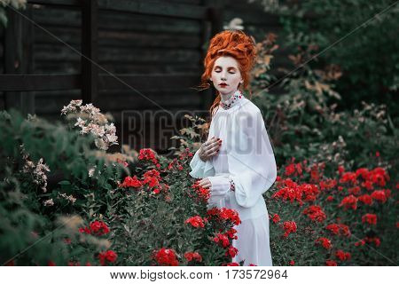 Beautiful vintage red-haired girl with a high hair in an old white dress in the garden. The Victorian era. Historic vintage costume. White Queen in garden. Princess castle. Garden with red flowers. Vintage style
