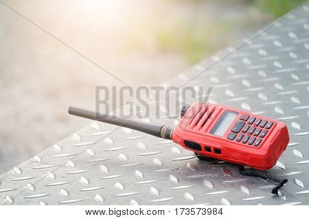Walkie Talkie radio transmitters or portable communication rests on a steel floor.