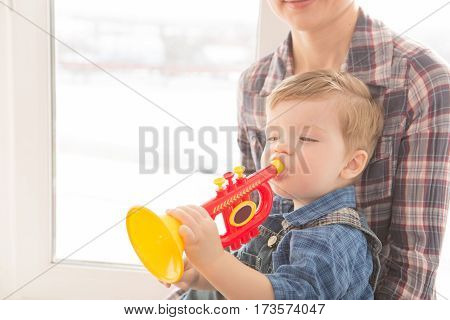 Kid And Mother Play Musical Toys.