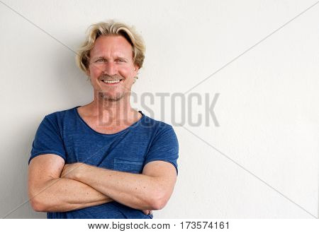 Happy Middle Aged Man Posing With Arms Crossed Against White Background