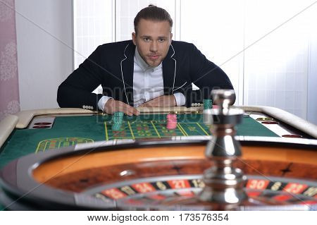 Portrait of a young handsome man playing in casino