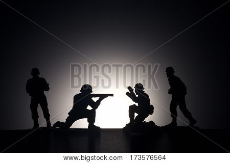 Silhouette of soldiers with rifle on a dark background