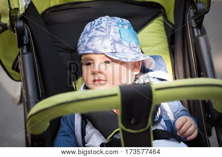 little and very beautiful baby boy sitting in the pram and waiting for mom