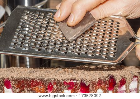 a person chocolate grating on the cake
