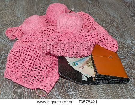 Skeins of yarn pink purse and money on a wooden background
