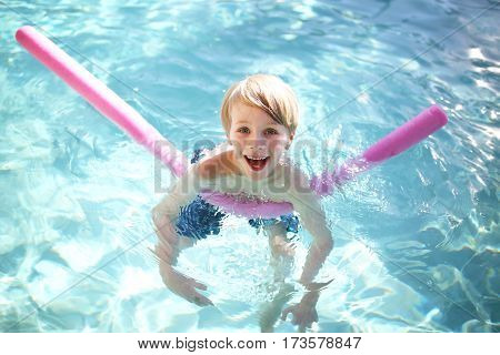 Happy Young Child Floating In Swimming Pool