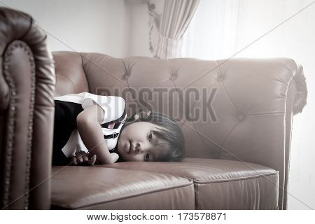 Asian child girl In lonely sad mood Alone on the couch