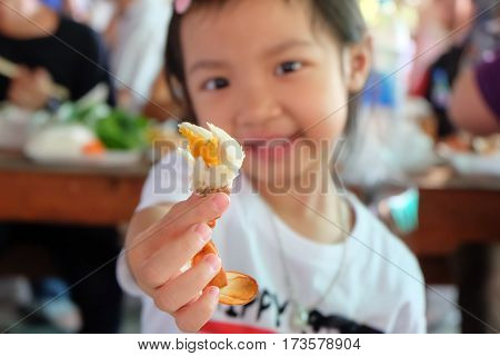 Asian child girl showing crab meat in hand with selective focus