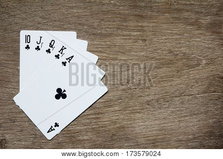 Five card of black club royal straight flush on wooden background