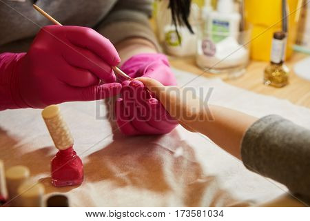 Little girl is getting manicure in beauty salon, close-up