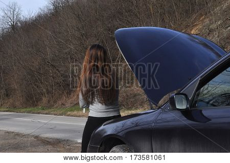 Woman opened the hood of broken car and wait for assistance on country roadside