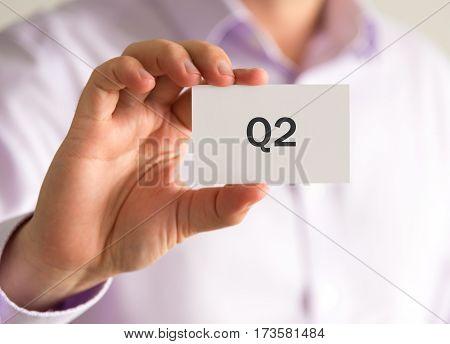 Businessman Holding A Card With Q2 Quarter 2 Message