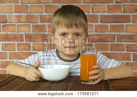 Cute little kid eating corn flakes on breakfast and drinking juice