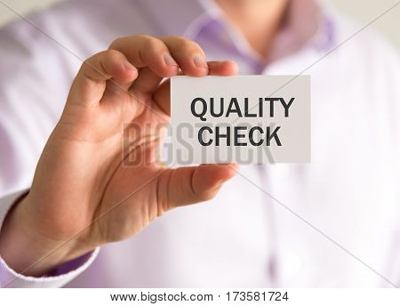 Businessman Holding A Card With Quality Check Message