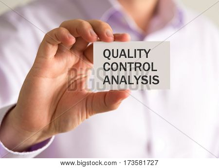 Businessman Holding A Card With Quality Control Analysis Message