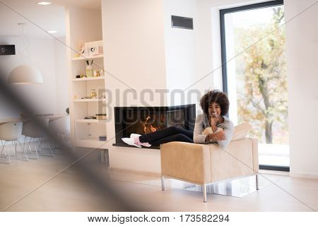 Young beautiful african american woman relaxing on chair in front of fireplace at autumn day