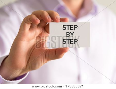 Businessman Holding A Card With Step By Step Message