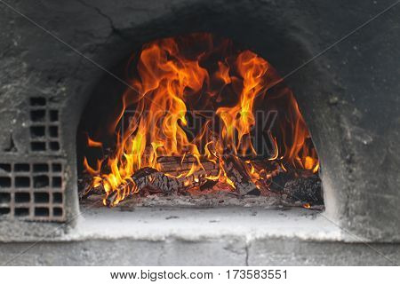 Wood burning firewood in the traditional stone oven.