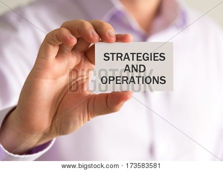 Businessman Holding A Card With Strategies And Operations Message