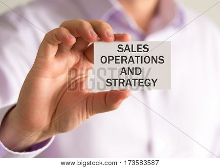 Businessman Holding A Card With Sales Operations And Strategy Message